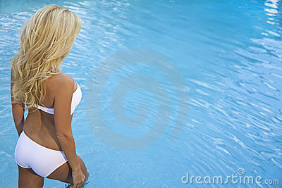 Sexy Blond Woman In Bikini Walking Into Blue Pool