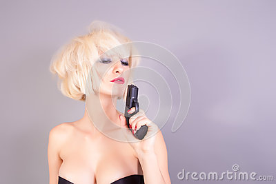 Sexy blond woman holding pistol gun
