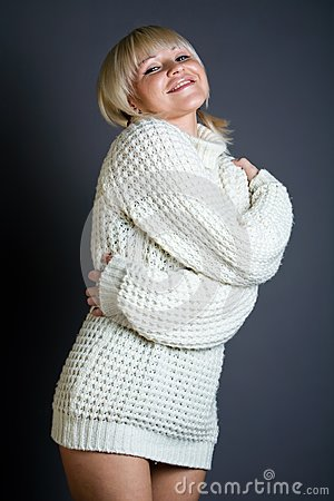 Sexy blond woman in sweater over gray background