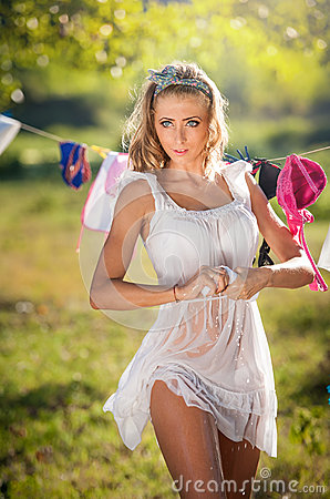 Free Sexy Blonde Woman In Wet White Short Dress Putting Clothes To Dry In Sun. Sensual Fair Hair Young Female Putting Out The Washing Royalty Free Stock Photos - 43333188