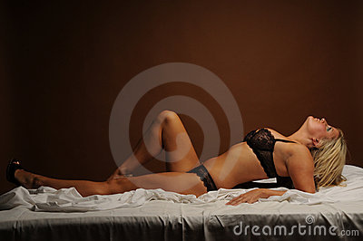 Sexy blonde woman laid on her bed