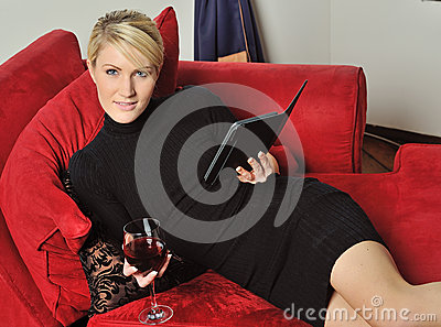 Sexy blonde woman reading an e-reader with wine