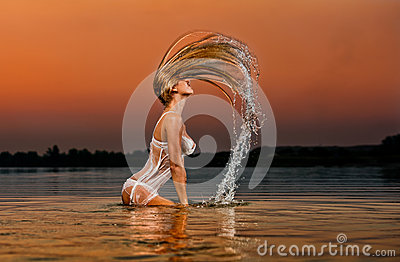 Sexy blonde woman in water at sunset
