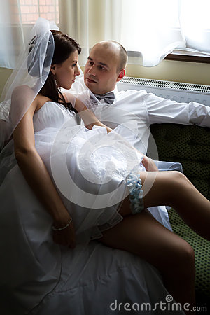 Sexy bride with groom on the sofa