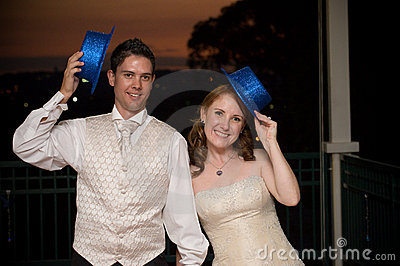 Sexy bride and young handsome groom with blue hats
