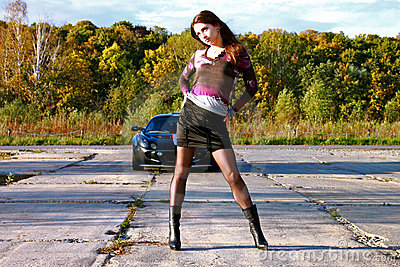 Sexy bright girl is standing in front of the auto