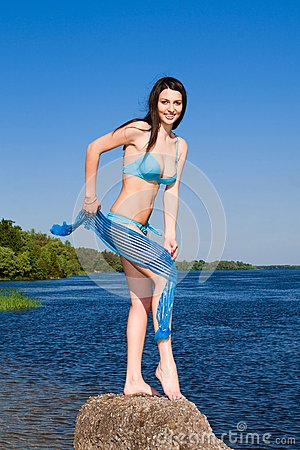 Sexy brunette against blue water