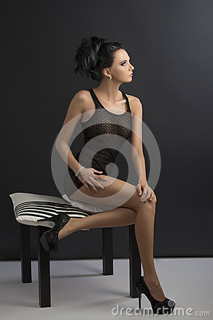 Sexy brunette is sitting on pillows, looks at left