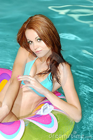 Sexy Brunette Woman Floating On Pool Toy