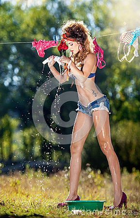 Free Sexy Brunette Woman In Bra And Denim Shorts Putting Clothes To Dry In Sun. Sensual Young Female With Long Legs Outdoor Stock Image - 43333231