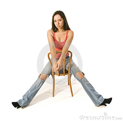 Sexy brunette woman sitting, torn jeans