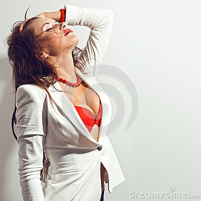 Sexy brunette woman touch her hair over white wall