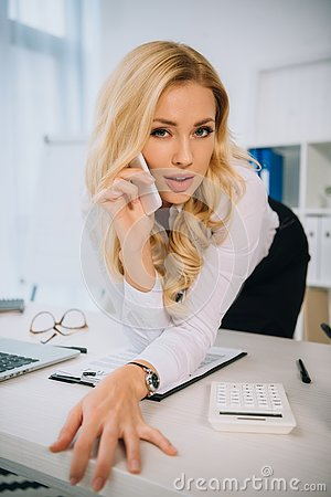Free Sexy Businesswoman Leaning On Table And Talking Stock Photography - 129235302