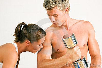 Sexy couple with dumbbells in gym