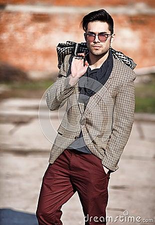 Sexy fashion man model dressed elegant holding a bag
