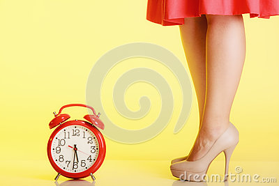 Sexy female legs in high heels and red clock. Time for femininity.