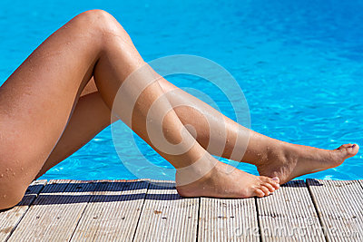 Sexy female legs at swimming pool
