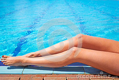 Sexy female legs at the swimming pool