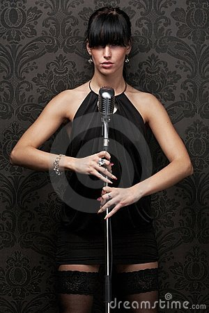 Sexy female singer wearing black dress holding a r