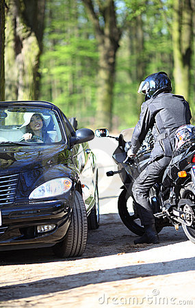 Sexy girl in car looking a man on a motorcycle