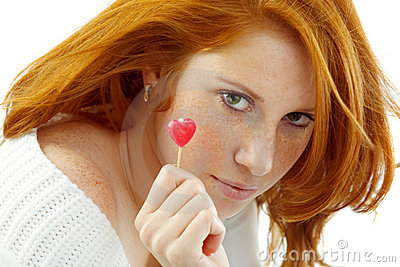 Sexy girl with red hair holding a heart