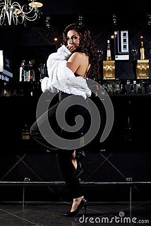 Sexy girl in retro fur coat stand near bar