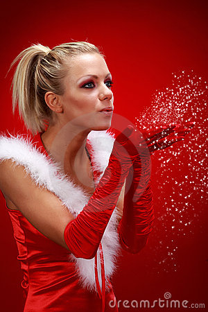Sexy girl in santa cloth blowing snow from hands.