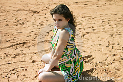 Sexy girl is sitting on the sand in green dress