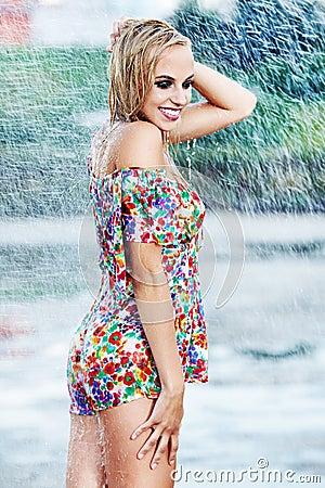 Sexy girl walking along wet street after rain