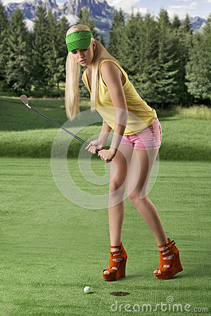 Sexy golf player woman, she is hitting golf ball