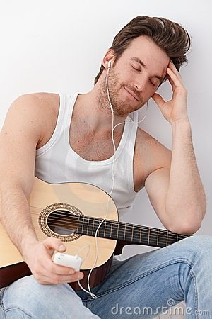 Sexy guitar player listening to music smiling
