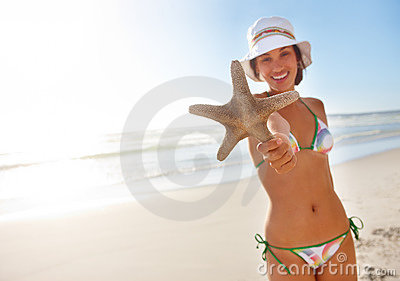 A sexy lady holding a starfish on the beach