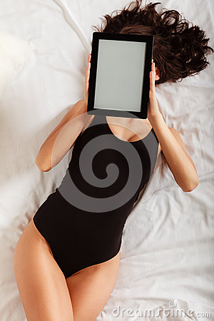 Sexy lazy girl lying with tablet touchpad on bed