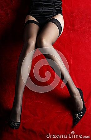 Sexy legs in erotic black stocking on red silk