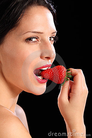 look by woman eating fresh strawberry fruit