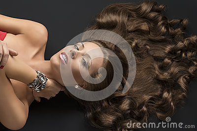 Sexy lying girl with long curly hair and hand on the neck