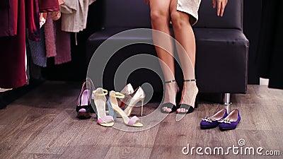 Sexy, met lange benen vrouw die op zwarte high-heeled sandals in een modieuze opslag, boutique proberen Langzame Motie Close-up stock video