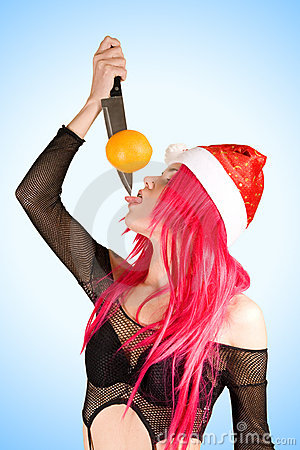 Sexy mrs. Santa with orange on the knife