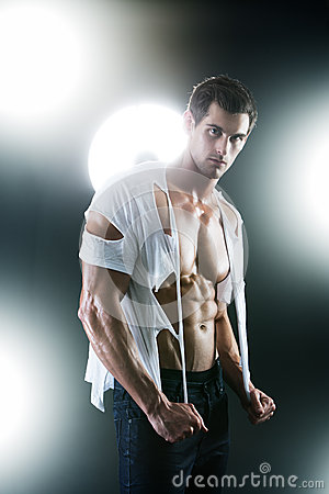 Sexy muscular male in white ripped shirt