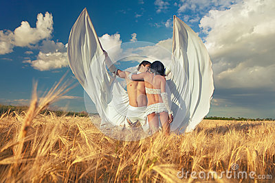 Lovers with white wings on wheat field