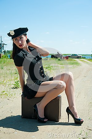 Sexy police woman sitting on old suitcase