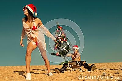 Sexy Santa helper  pulling Santa at the beach