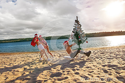 Sexy Santas  pulling Santa at the beach