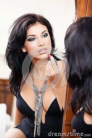 Sexy sensual woman applying lipstick