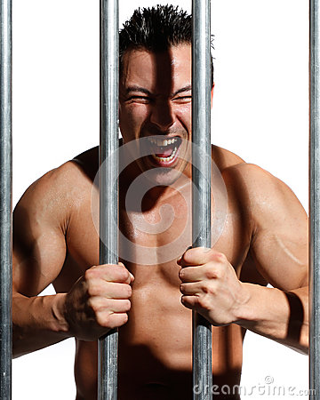Sexy shirtless man behind bars on white background