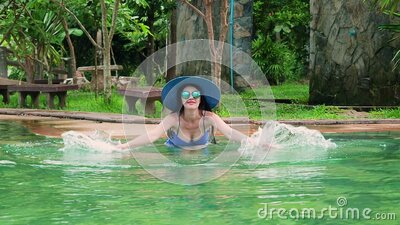 Sexy sllim girl in a blue swimsuit, hat and sunglasses swimming in the thermal pool on a sunny day. Slow motion Young stock video
