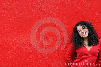 Sexy smiling girl wearing red on red wall