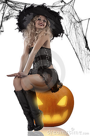 Sexy witch sitting on a pumpkin