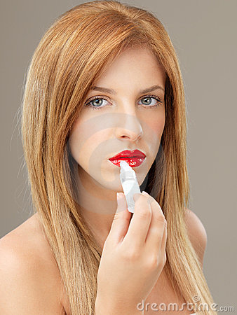 Sexy woman applying shiny lip gloss