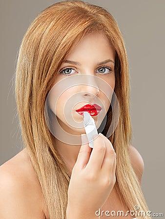 Sexy woman applying shiny lip gloss